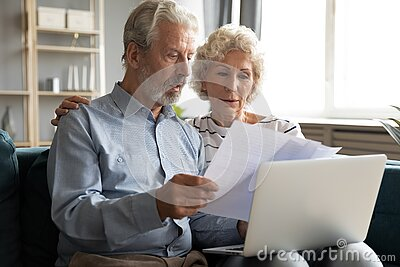 Serious older couple managing budget together, reading documents