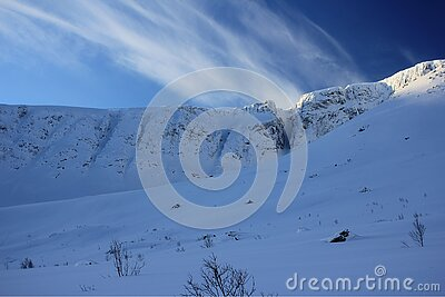snowcovered rocks under clouds