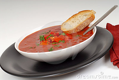 Tomato, red pepper, basil soup in white bowl with bread and spoo