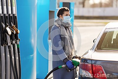 Woman in mask filling her car at gas station