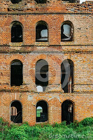 Red brick wall of abandoned building with arched windows