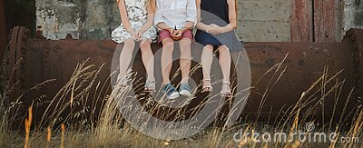 Close up of children`s legs, three siblings sitting on a rusty pipe