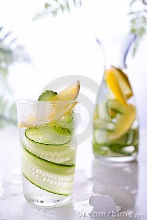 Cold and refreshing infused detox water with lemon and cucumber in a glas. Homemade flavored lemonade