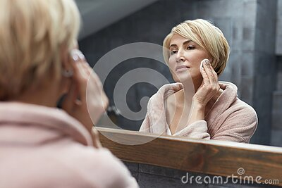 Skincare Routine. Anti Aging Beauty Treatment Concept. Mature Woman Cleans Face Skin With Cotton Pads.