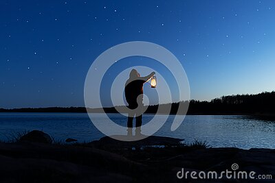 Man holding the old lamp outdoors near the lake. Hand holds a large lamp in the dark.