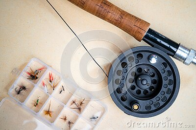 Close up of fly fishing rod with reel next to box with tied flies. Fly fishing equipment still life. Nobody