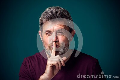 A portrait of bearded man showing hush gesture. People and emotions concept