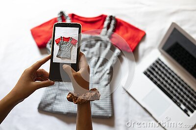 Woman taking a photo of an article of clothing to sell online. Concept of selling clothes online.