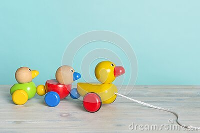 Wooden toy ducks a kids toy to pull around against a blue background with space for copy
