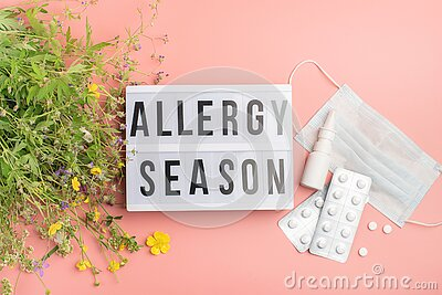 The concept combating preventing seasonal allergies. Fresh flowers medical mask pills drops medicine pink background.
