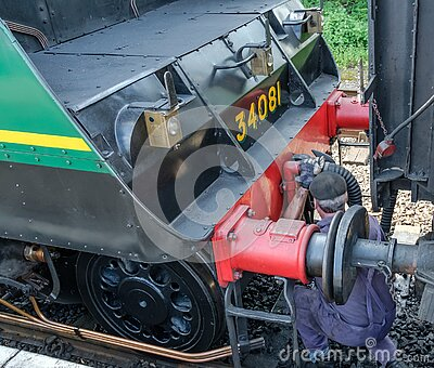Steam engine driver seen crouching in front of his steam train, de-coupling a passenger car.