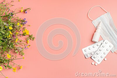 The concept combating preventing seasonal allergies. Fresh flowers medical mask pills drops of medicine pink background