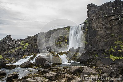 Smooth silky water on Pingvellir waterfall Oxarafoss in Iceland