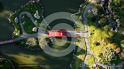 An aerial top-down view on Japanese styled garden with red bridge