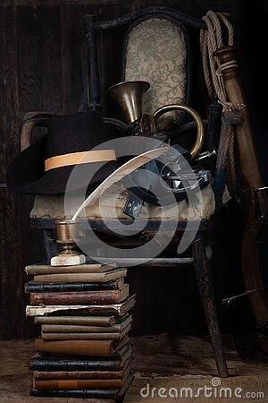Adventure fiction - Vintage old broken wooden chair with hat, sword, bugle, books and fountain pen with inkpot