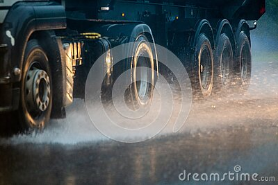 Rain water splash flow from wheels of heavy truck moving fast in daylight city with selective focus.