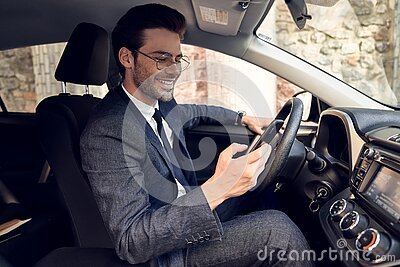 Side view of serious business man in suit using phone while sitting at the wheel in car