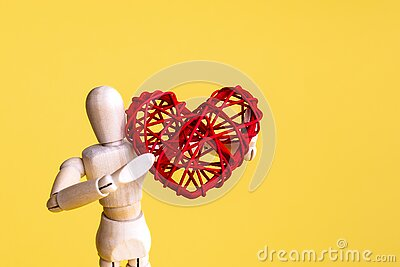 Wooden mannequin holding rattan red heart. Yellow background