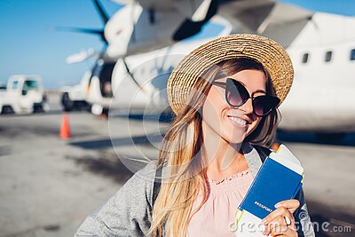 Woman traveler boarding on plane holding passport tickets. Happy passenger with backpack ready for flight