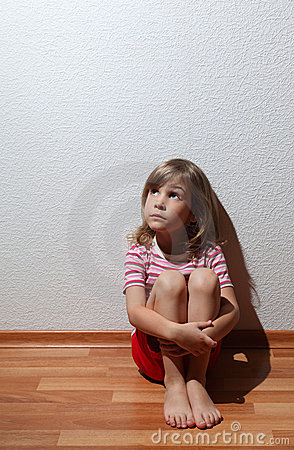Little girl in casual clothes looks sad to corner
