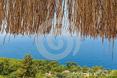 Texture of dry straw on the roof of view with a blue sea background. holiday background