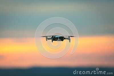 Drone pilotage on the sky at sunset