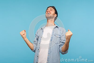 Euphoria from victory. Portrait of delighted enthusiastic man in worker denim shirt screaming for joy