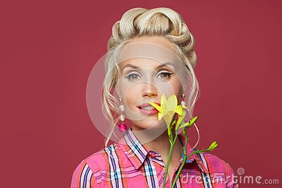 Pretty pinup woman with yellow flower on red background