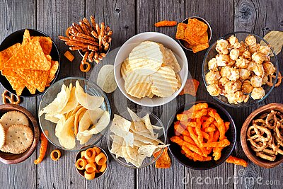 Assortment of salty snacks, top view table scene over wood