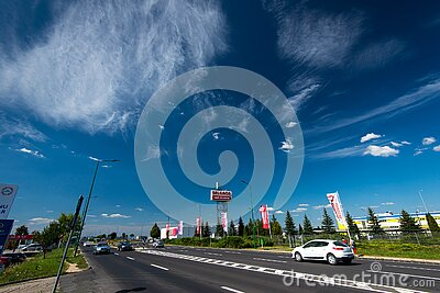 Wide angle shot, Selgros street sign, passing cars, blue sky with white clouds.