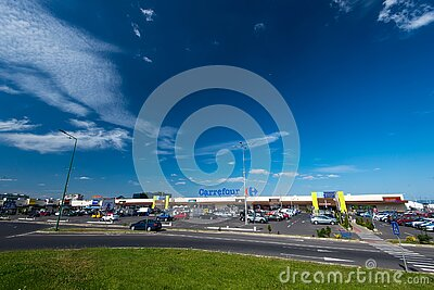 Wide angle shot, Carrefour store front with parking lot, blue sky with white clouds.
