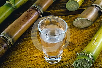 Glasses of Brazilian gold and white cachaça on rustic wooden background. Typical alcoholic drink from Brazil