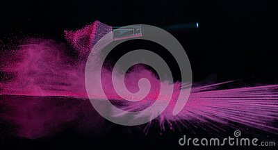 Pink makeup powder brush fall on shiny black surface in a dust cloud