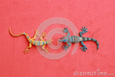 Closeup shot of small toy geckos isolated on a red background