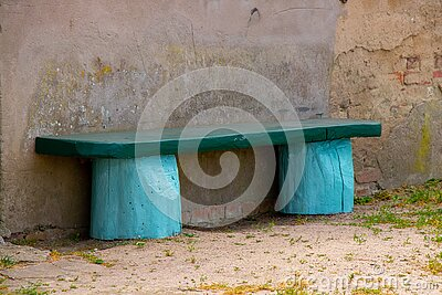 Closeup of a mint green bench made from a tree near the wall