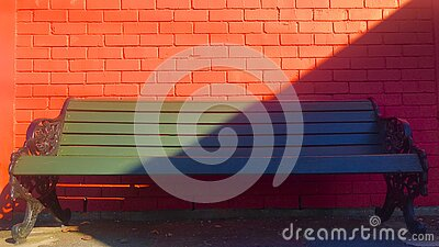 Green bench and red brick wall with oblique shadow.