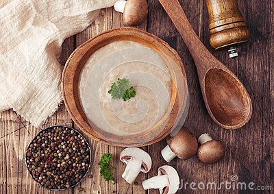 Wooden plate of creamy chestnut champignon mushroom soup with wooden spoon, pepper and kitchen cloth on wooden background. Top