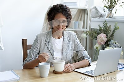 Happy young businesswoman adding refined sugar to cup of coffee.