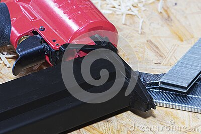 Red pneumatic construction stapler and a stack of staples for the stapler.
