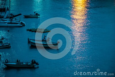 Yachts and boats in the bay. Reflection of light from a lantern on the water.