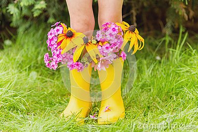Child`s feet in rubber yellow boots with autumn flowers in it