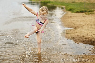 Little cute girl have fun playing with a spray of water in the river at summer. copy space