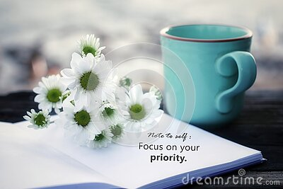 Note to self. Focus on your priority. Self motivation concept on flat lay vintage background with notebook flowers and coffee cup.