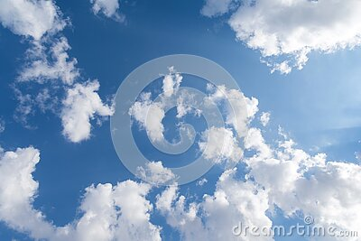 Wide angle perspective shot of clean blue limitless sky with clouds. Rays of the sun highlight the clouds