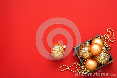 Christmas decorations. Gold baubles and beads in the wooden box on the red background with copy space.