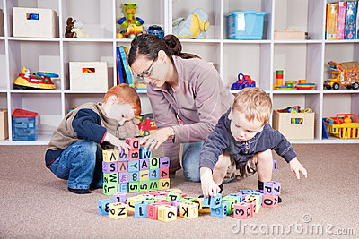 Babysitter playing kids block game with children