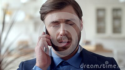 Serious business man speaking mobile phone at home office. Guy talking phone.