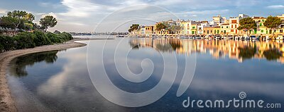 Panorama of Portocolom harbour with boats, traditional houses and calm sea with reflection, Mallorca, Spain