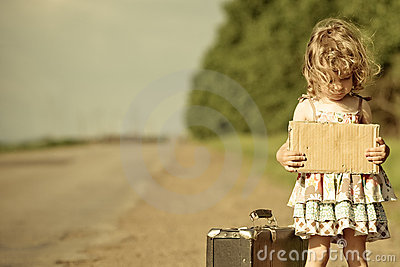 Lonely girl with suitcase standing about road