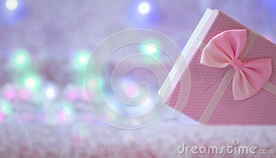 Christmas gift box of soft pink color on a defocused background with burning lights of a garland. Christmas background. Free space